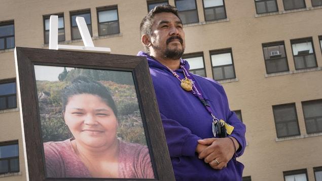 Carol Dubé devant l'hôpital de Joliette en compagnie d'une photo de la mère de famille, un an après la mort de celle-ci.