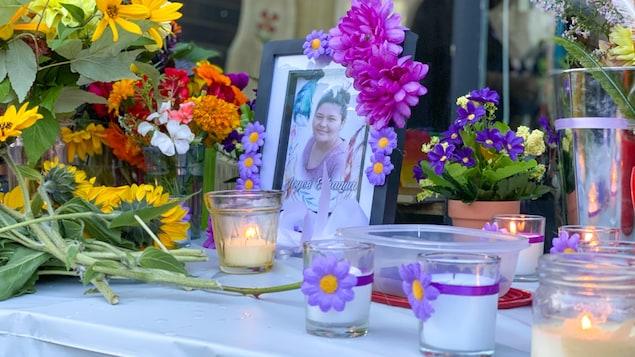 Une table avec des chandelles et une photo de Joyce Echaquan avaient été installés pour que le gens puissent y déposer des fleurs.
