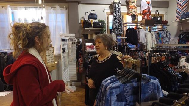 La mère de la propriétaire aidant un client dans le magasin.