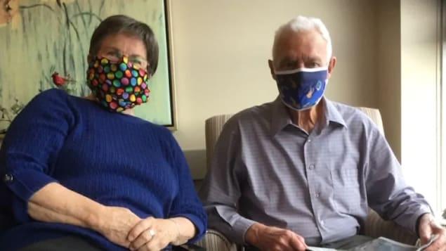 Judith Hodgson et son mari, Camil Dufort, portant des masques.