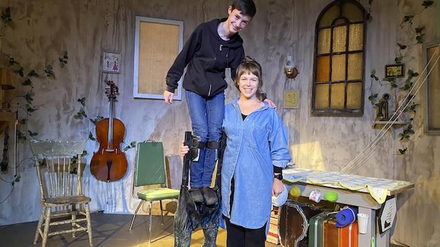 Une accolade entre Judy Wensel et Lazlo Paradis, ce dernier est  perché sur des échasses. Ils sont entourés du décor de la pièce de théâtre.