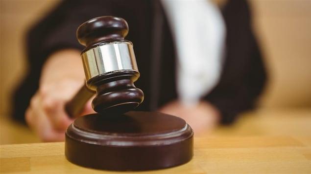 Un juge frappe son marteau.