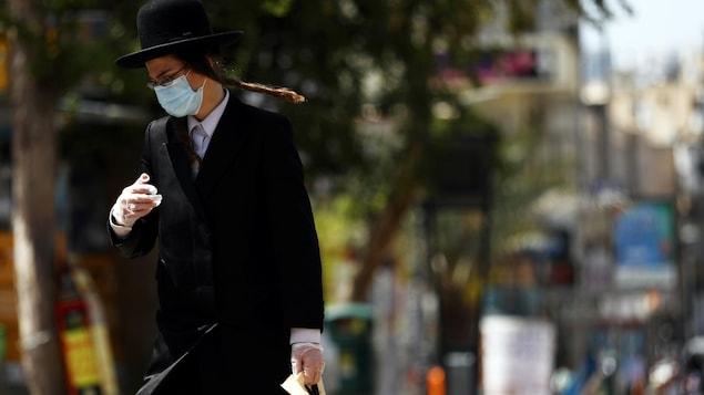 L'homme, qui porte un masque et des gants, traverse la rue