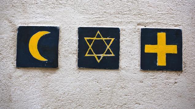 Des symboles des trois plus importantes religions monothéistes dans le monde posés sur un mur en signe de paix.