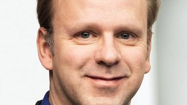 L'homme qui porte un veston gris foncé sur une chemise bleu sourit à la caméra