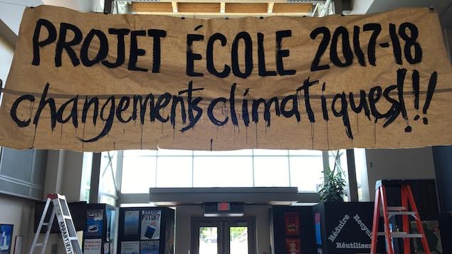 Une bannière en papier, où il est écrit «Projet d'école 2017-18, changements climatiques!», est accrochée au plafond du hall de l'école.