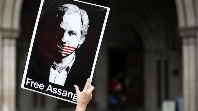 Une personne tient une affiche sur laquelle se trouve le portrait de Julian Assange muselé par un drapeau américain.