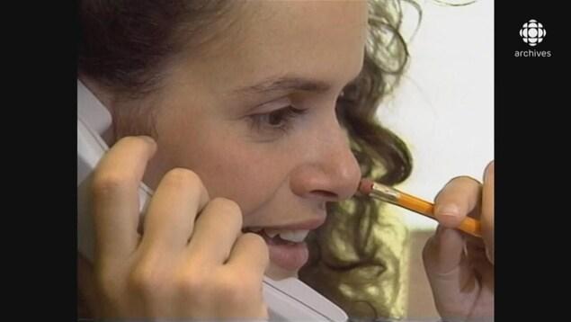 Julie Payette discutant au téléphone et jouant avec un crayon à mine posé sur son nez