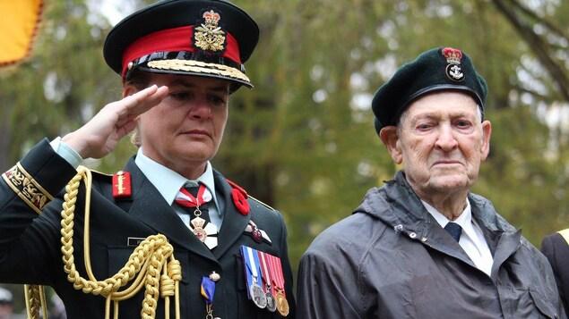 Julie Payette fait le salut militaire aux côtés d'un vétéran.
