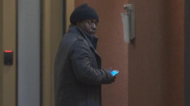Un homme portant un manteau et une tuque dans un corridor.