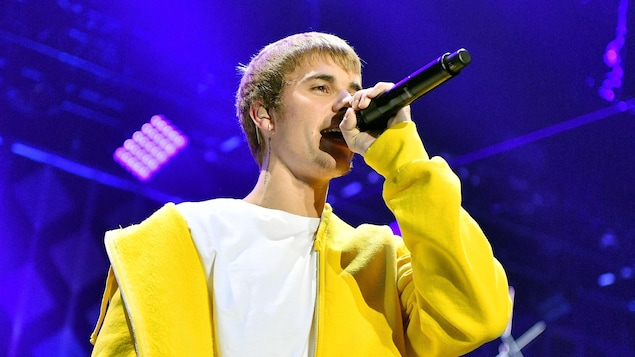 Justin Bieber, microphone à la main, chante sur scène lors d'un concert.