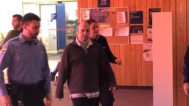 Justin John Bresaw marche dans l'entrée du palais de justice accompagné de deux agents.