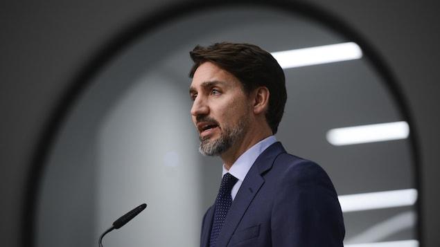 Plan moyen de Justin Trudeau devant un micro.
