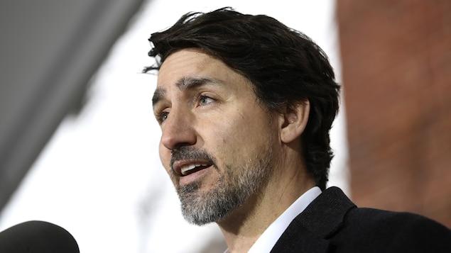 Justin Trudeau, de profil, parle dans un micro.