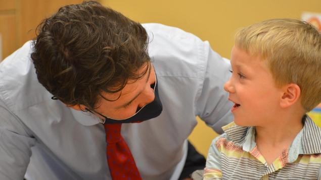 Justin Trudeau joue avec un jeune enfant dans une garderie.