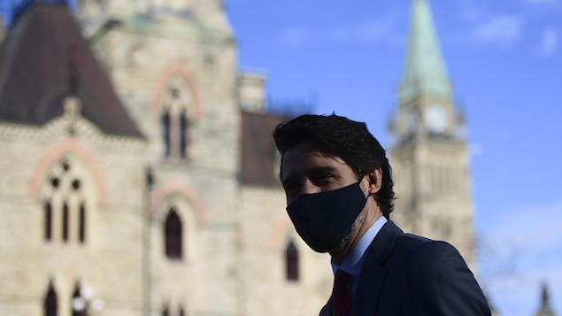 Justin Trudeau, masqué, près du parlement.