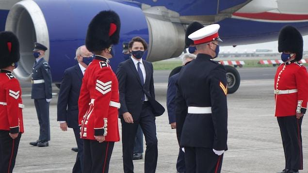 Justin Trudeau marchant entre des rangées de militaires britanniques.
