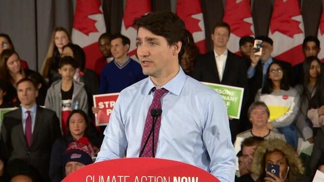 Justin Trudeau debout au podium, alors qu'on voit plusieurs partisans libéraux derrière lui.