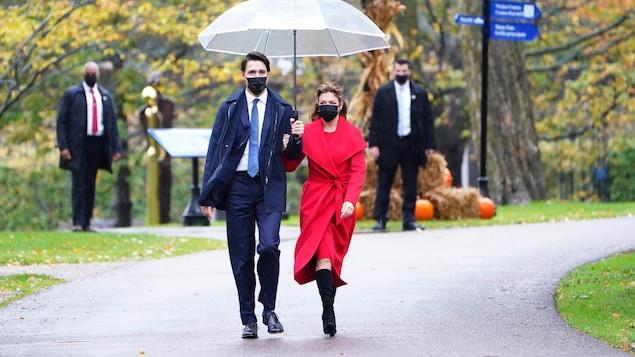 Justin Trudeau et sa conjointe Sophie Grégoire Trudeau marchent dehors sous un parapluie.