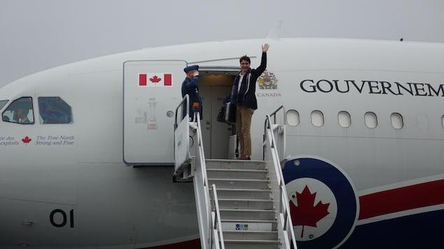 Le premier ministre fait un salut de la main, en haut d'un escalier, juste avant d'entrer dans l'appareil.