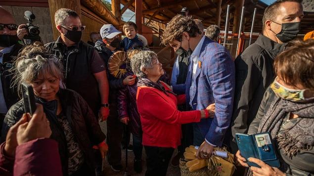 Hawak sa baywang ng isang matandang babae si Justin Trudeau na napapaligiran ng mga tao.2021年 10 月 18日,在坎卢普斯前原住民寄宿学校外,加拿大总理贾斯汀·特鲁多与一名原住民妇女交谈。