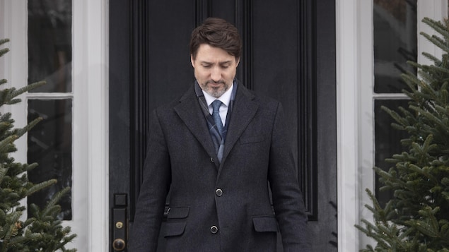 Justin Trudeau sort d'une maison.