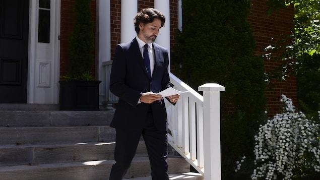 Justin Trudeau sort de sa maison en tenant des feuilles de papier.