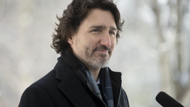 Justin Trudeau, dehors, derrière un micro durant un point de presse.