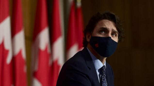 Justin Trudeau, portant un masque, assis devant des drapeaux canadiens pour une conférence de presse.