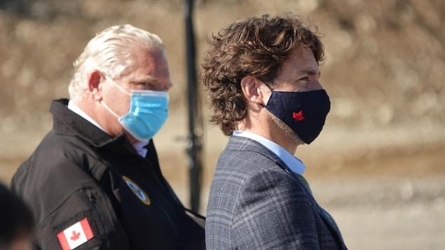 Justin Trudeau assis près de Doug Ford; les deux hommes portent un masque.
