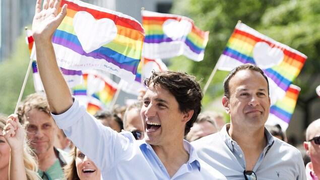 Tout sourire, Justin Trudeau salue la foule, au milieu de citoyens et de drapeaux.