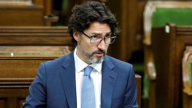 Assis au Parlement, Justin Trudeau jette un coup d'oeil au-dessus de ses lunettes.