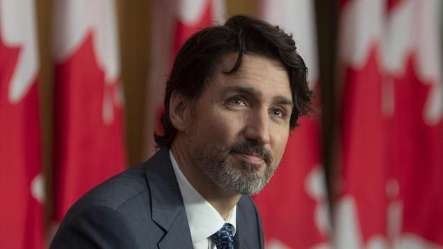Justin Trudeau devant des drapeaux du Canada.