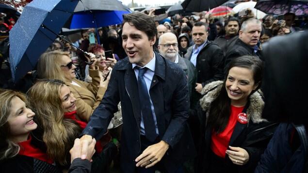 Justin Trudeau traverse la foule, sous la pluie, en serrant des mains et en souriant.