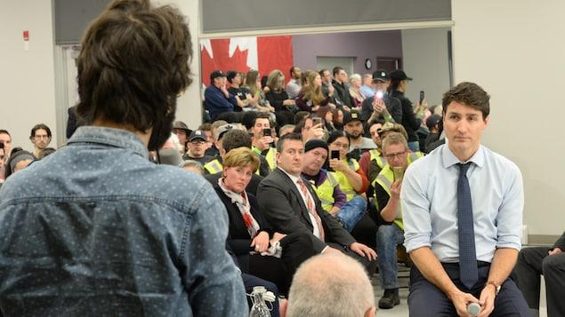 Justin Trudeau écoute la question d'un participant au rassemblement populaire