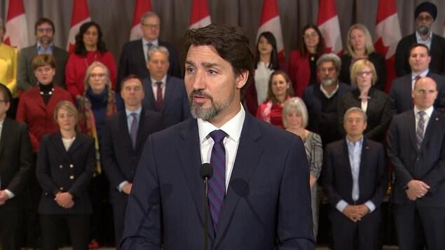 Justin Trudeau parle en conférence de presse. Ses ministres se tiennent debout derrière lui.