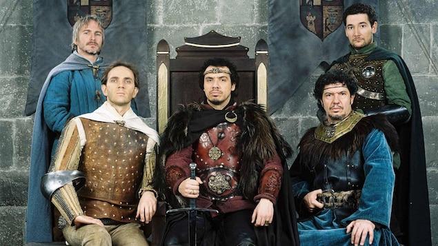 Quatre acteurs en costumes médiévaux se tiennent autour d'un trône où est assis Alexandre Astier, dans son rôle du roi Arthur de la série <em>Kaamelott</em>.