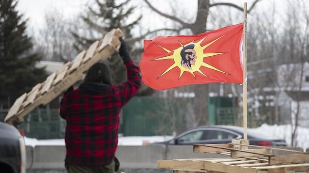 Un homme transporte une palette de bois, un drapeau mohawk flotte tout près.