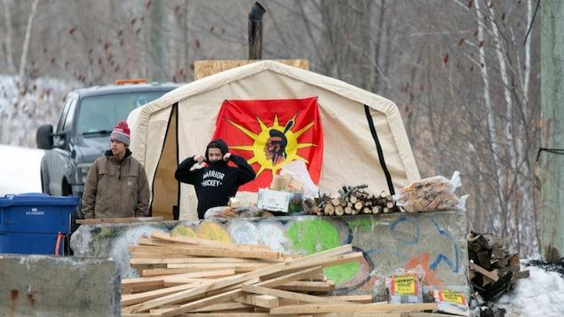 Des Autochtones derrière des planches de bois et des murets de béton constituant une barricade.