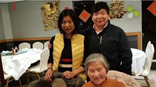 Kai Huang, un homme originaire d'Ottawa, sa  femme et sa mère posent à la table d'un restaurant.