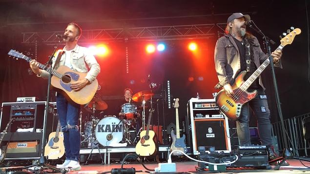 À gauche sur scène, un homme gaucher joue de la guitare sèche en chantant, au centre, un autre joue de la batterie au centre en souriant, alors qu'un troisième joue de la basse en chantant aussi.