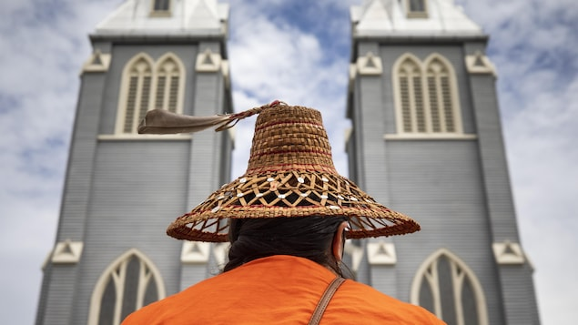 Un membre de la Nation Squamish, en Colombie-Britannique, vue de dos devant une église.