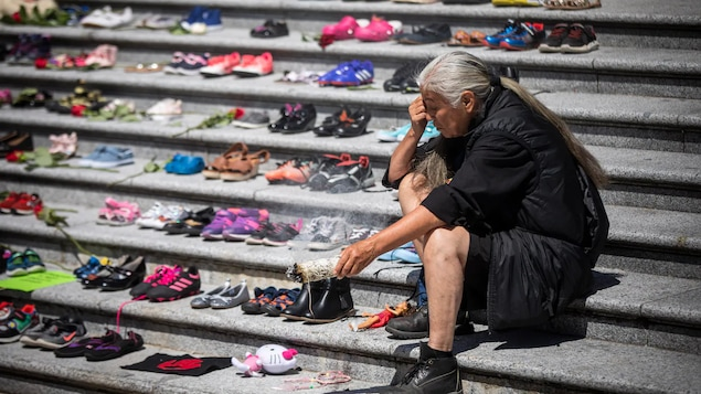 Une femme autochtone se recueille près de souliers d'enfants déposés sur des marches en ciment.