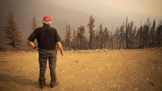 Ron Ignace devant une forêt brulée.