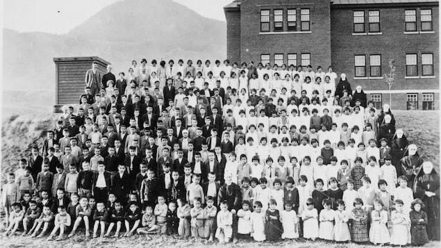 Environ 300 enfants et le personnel du pensionnat posent devant l'édifice.