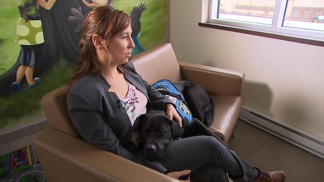 Le chien Kanak et sa maîtresse sont assis sur un divan.