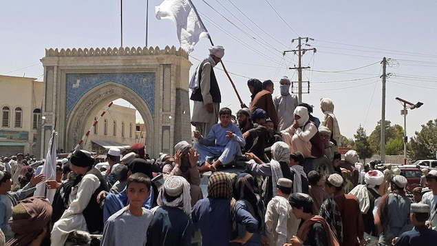 Des dizaines de personnes sont massées autour d'un véhicule sur lequel se tiennent des hommes. Un drapeau s'élève au-dessus des têtes.