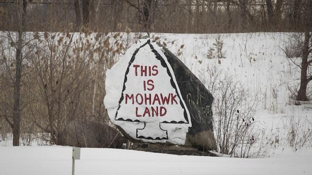 Un dessin sur une pierre, sur laquelle est peint « This is mohawk land ».