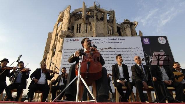 Le musicien est accompagné d'autres musiciens devant un bâtiment en ruines.