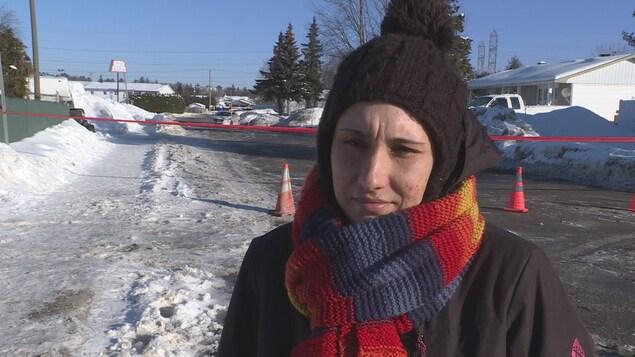 Karine Jolicoeur, une dame habillée en tenue hivernale, lors d'une entrevue devant un ruban de police qui ferme une rue.